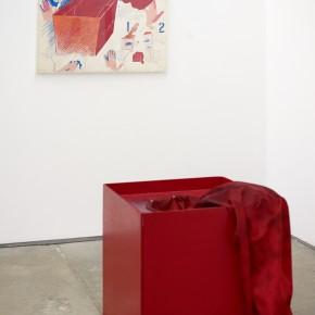Vista en sala | Diego Barboza |Poema gestual | 1981| Caja Roja con manga roja y líquido azul en su interior ; Indicaciones para realizar la acción, témpera, creyón y grafito sobre cartulina | 70 x 70 x 70 cm (caja roja) 70 x 100 cm (indicaciones para realizar acción