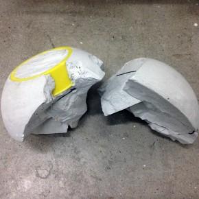 16. Amuleto | 2014 | Pedazos sobrantes de la ejecución de la obra Escultura rápida proyectada, vaciados en yeso con cemento gris y aro de plástico amarillo | 14 x 25 x 13 cm